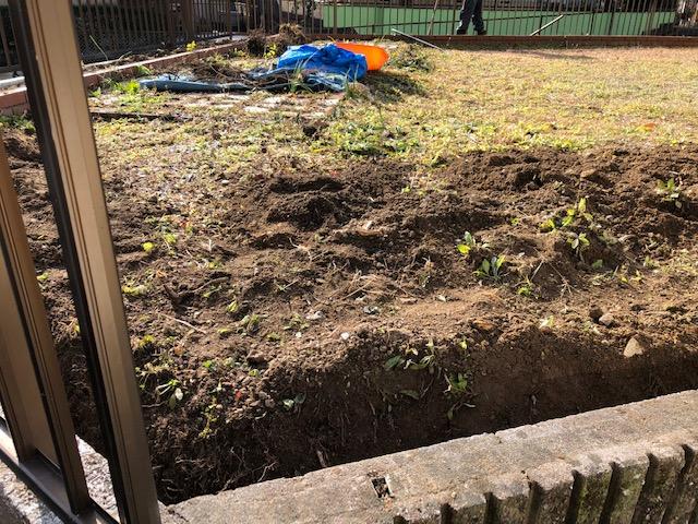お客様の不動産の庭に防草シートを敷く準備をする